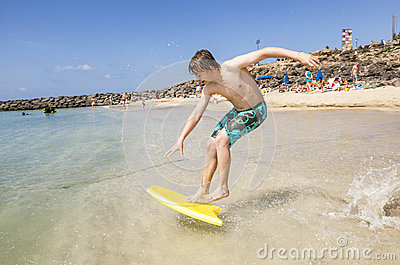 Boy jumps into the ocean with his boogie board