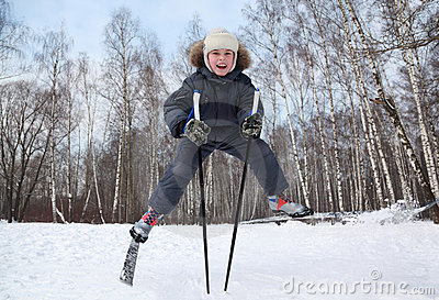Boy jumps and spreads legs on cross-country skis