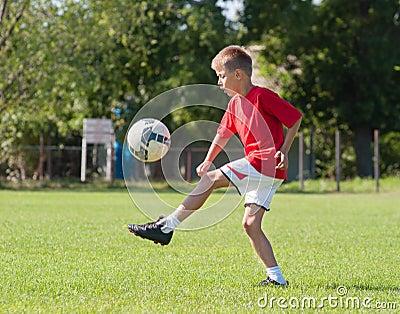 Boy kicking football