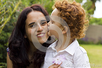 Boy kissing mother on her cheek