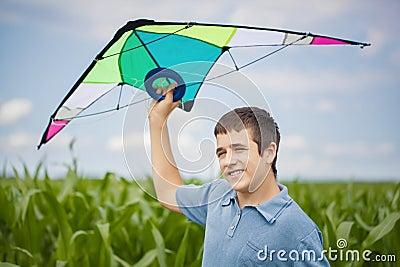 Boy with kite on a corn field
