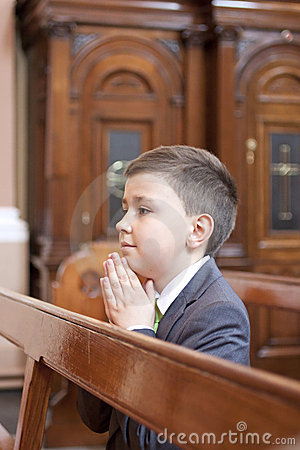 Boy kneeling and praying in the church.