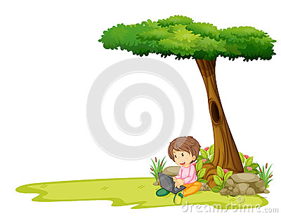 A boy with a laptop under a tree