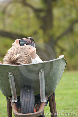 Boy Laying Wheelbarrow Using Mobile Phone