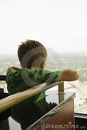 Boy leaning on railing.