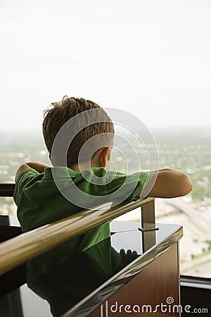 Boy leaning on railing.