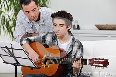 Boy learning to play the guitar