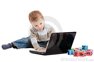 Boy learning to read with kids blocks and computer