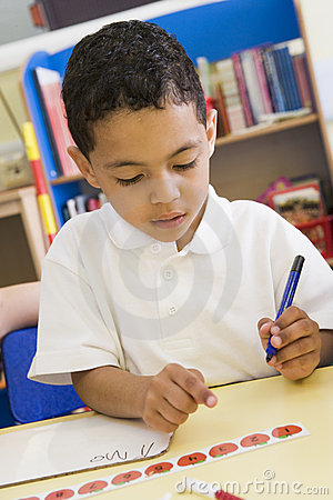 Boy learning to write numbers in primary class