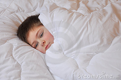 Boy lies in bed covered with a blanket