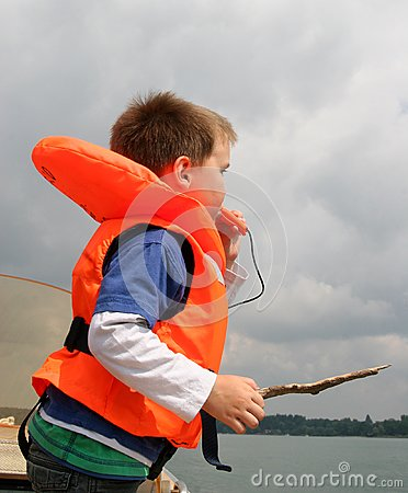 Boy in life vest blowing a whistle