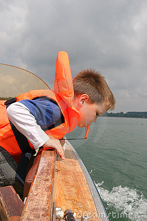Boy in life vest leaning over boat railing