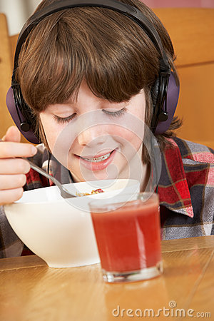 Boy Listening To MP3 Player Whilst Eating