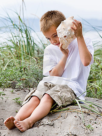 Free Boy Listening To Seashell At Beach Royalty Free Stock Images - 7423079