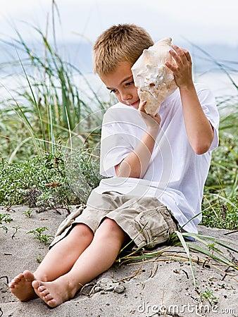 Boy listening to seashell at beach