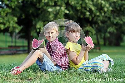 Boy and little girl eat watermelon