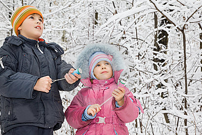 Boy and little girl with petard in hands in winter