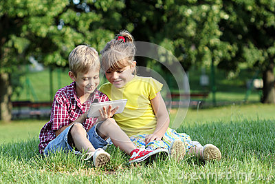 Boy and little girl play with tablet in park