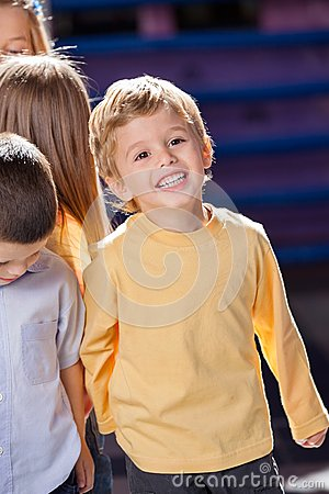 Boy Looking Away With Friends In Kindergarten