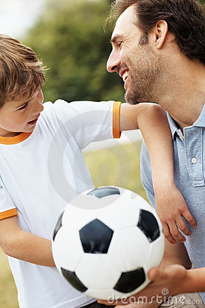 Boy looking at his smiling father holding football
