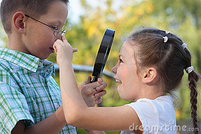 Boy is looking at joyful girl through magnifier