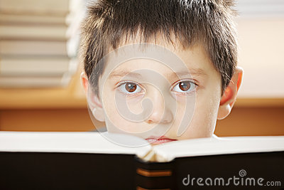 Boy looking over book