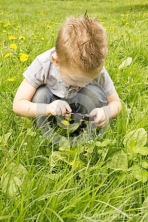 Free Boy Looking Through A Magnifying Glass On The Grass Royalty Free Stock Photo - 40898045