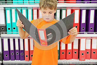 Boy looks big folder and stands near to shelves