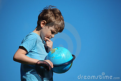 Boy looks on globe against sky