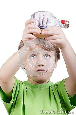 Boy looks at miniature model of tallship in bottle