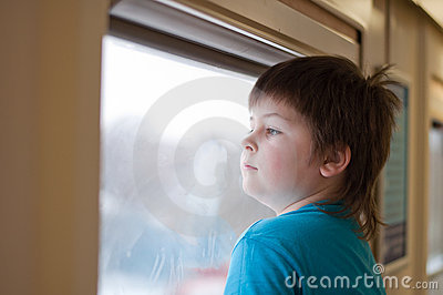 boy looks out the window the train
