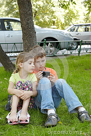 Boy looks at phone screen, sister sits next to him