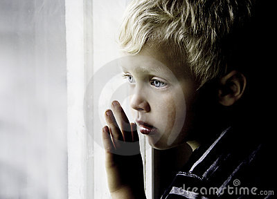 Boy looks sadly through window