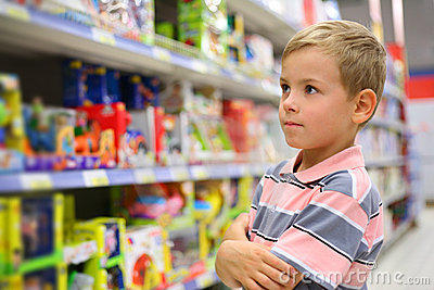 Boy looks at shelves with toys