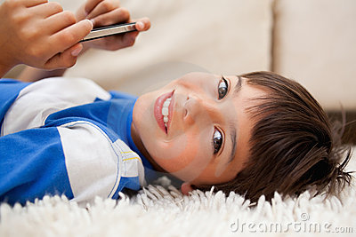 Boy lying on the carpet with cellphone