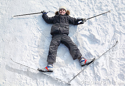 Boy lying in cross-country skis on snow