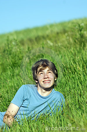 Boy lying on the fresh green grass