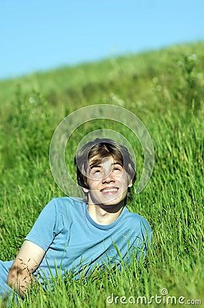 Boy lying on the fresh green grass