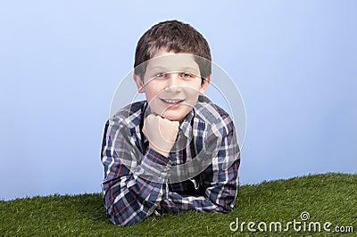 Boy lying on a grass field