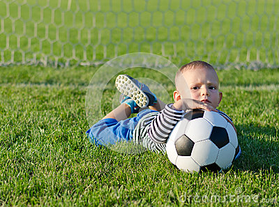 Boy lying on grass with soccer ball