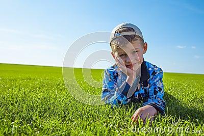 Boy lying on green grass