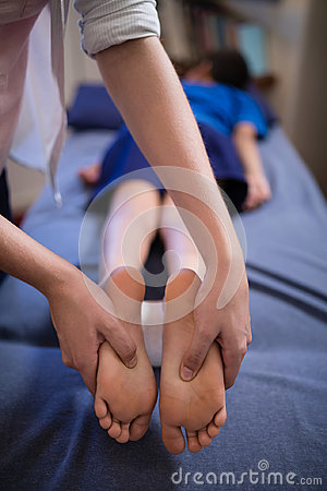 Free Boy Lying On Bed While Receiving Foot Massage From Young Female Therapist Royalty Free Stock Image - 96124586