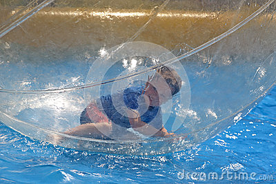 Boy lying in water sphere