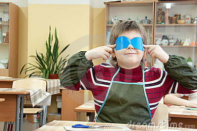 Boy makes a masquerade mask in class at school