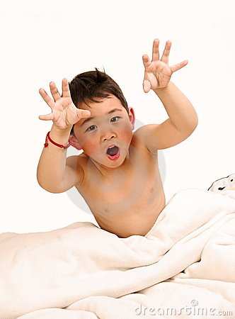 Boy making faces on bed