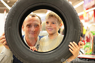 Boy and man look into vehicle tire