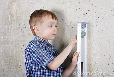 Boy measuring vertical of wall by level