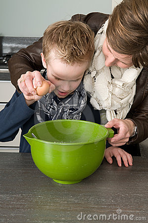 Boy and mother making the dough for the cakes