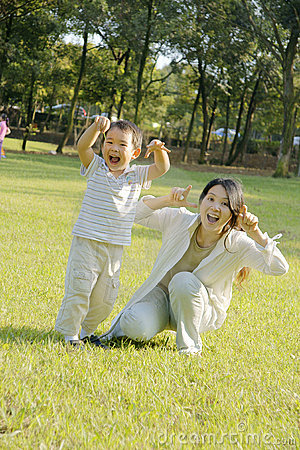 Boy and mother making faces on lawn