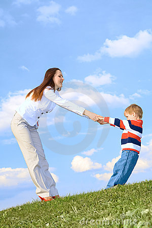 Boy with mother playing at blue sky background